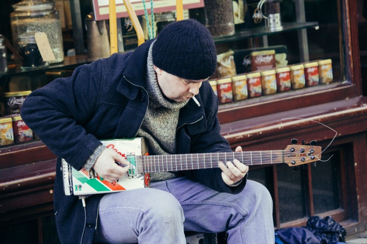 A man playing on his selfmade guitar.